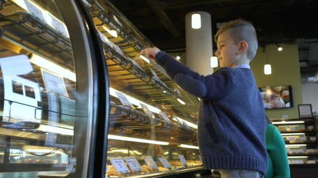 mother and son looking at a display case in a bakery - display cabinet stock videos & royalty-free footage
