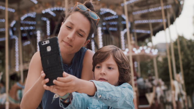 mother and son looking at mobile phone together - real people stock videos & royalty-free footage