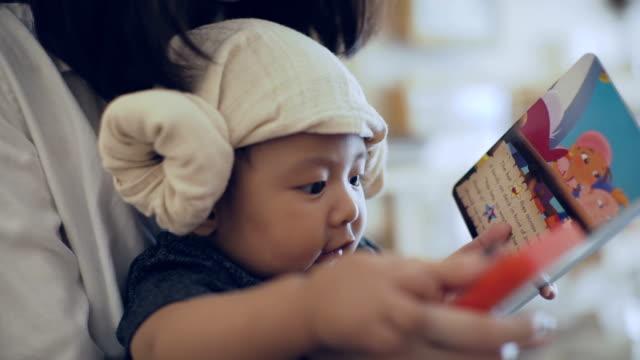 cu: mor och son (6 månader) tittar på bilderbok, thailand - 6 11 månader bildbanksvideor och videomaterial från bakom kulisserna