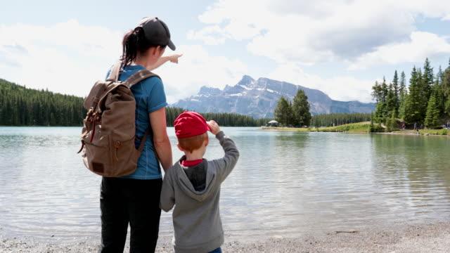 mutter und sohn mit blick auf den two jack lake im banff national park, alberta, kanada - mütze stock-videos und b-roll-filmmaterial