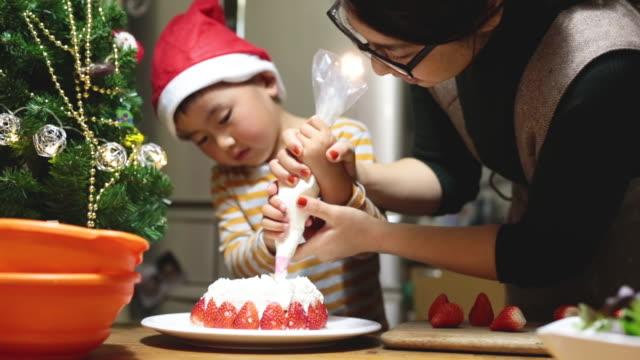 自宅でクリスマスケーキを作る母と息子 - decoration点の映像素材/bロール
