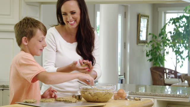 vidéos et rushes de mother and son making cookies in the kitchen, panning shot - 40 44 ans