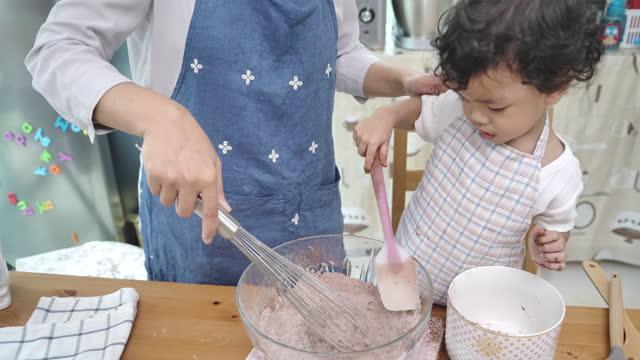 vídeos y material grabado en eventos de stock de madre e hijo haciendo cupcakes juntos. - son