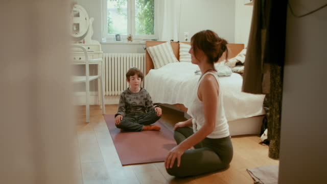 vídeos y material grabado en eventos de stock de mother and son meditating in bedroom - mid adult women