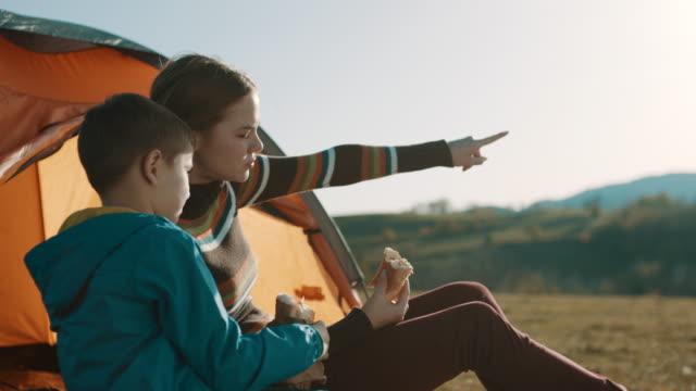 stockvideo's en b-roll-footage met moeder en zoon op camping trip zit aan de tent en het eten van een broodje - broodje voedsel