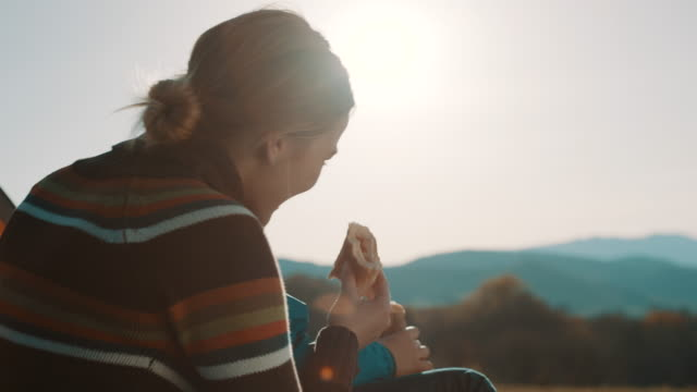 mother and son on camping trip sitting in front of the tent and eating a sandwich - panino ripieno video stock e b–roll