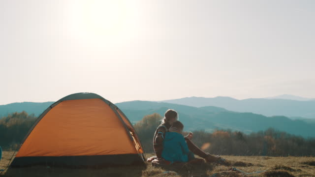 mother and son on camping trip sitting in front of the tent and eating a sandwich - camping stock videos & royalty-free footage