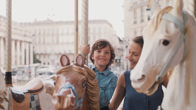 mother and son on carousel horses - reportage stock videos & royalty-free footage