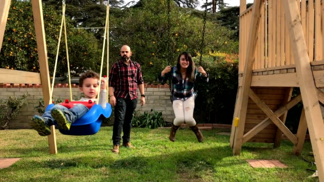 mother and son on swing set - domestic garden stock videos & royalty-free footage