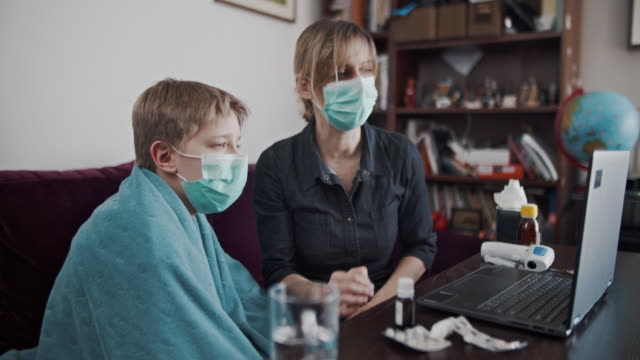mother and son on telemedicine video call with doctor - remote location stock videos & royalty-free footage