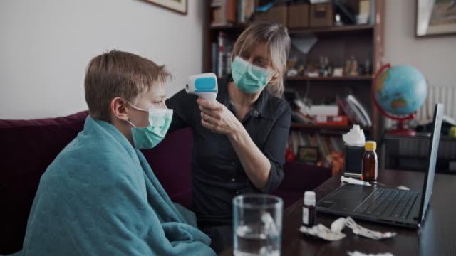 医師との遠隔医療ビデオ通話の母と息子 - 温度計点の映像素材/bロール