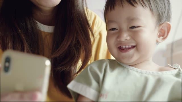 vídeos de stock e filmes b-roll de mother and son on video call with father hospital. - sudeste asiático