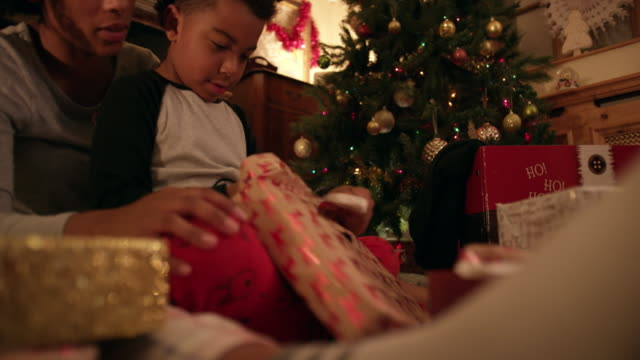 mother and son opening gift - christmas tree stock videos & royalty-free footage