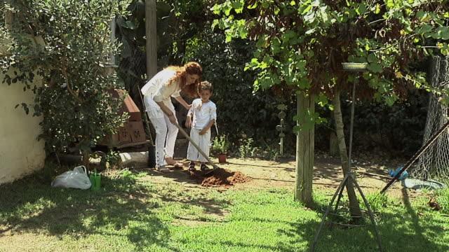 vidéos et rushes de ws mother and son (4-5) planting  tree in back yard on tu bishvat / beit yitzhak, israel - plante