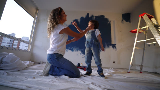 vídeos de stock e filmes b-roll de mother and son playing around with paint during a home renovation having fun laughing and painting their faces - equipamento