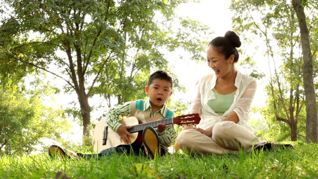 mother and son playing guitar in the park - soloist stock videos & royalty-free footage