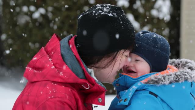 Moeder en zoon spelen buiten in de Winter sneeuwstorm