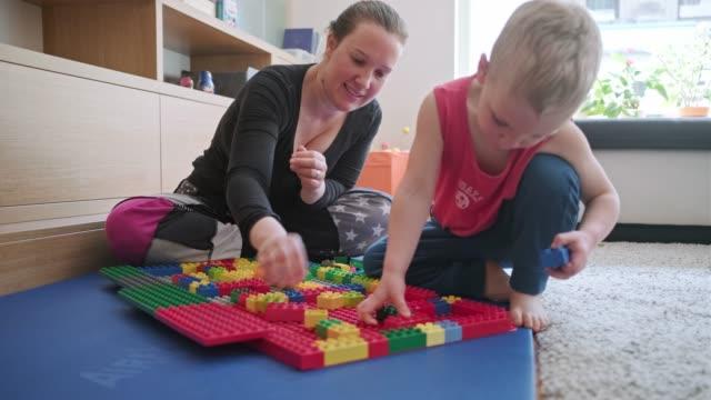 vídeos y material grabado en eventos de stock de madre e hijo jugando con bloques de juguete - liubliana