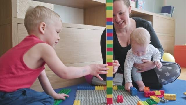 vidéos et rushes de mère et fils jouant avec des blocs de jouet - jeu de construction