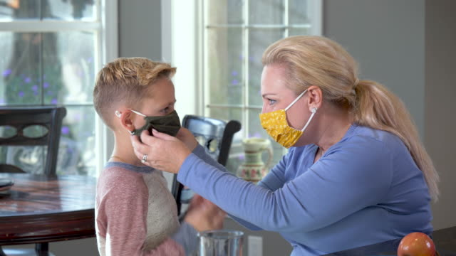 mother and son putting on face masks - 8 9 years stock videos & royalty-free footage