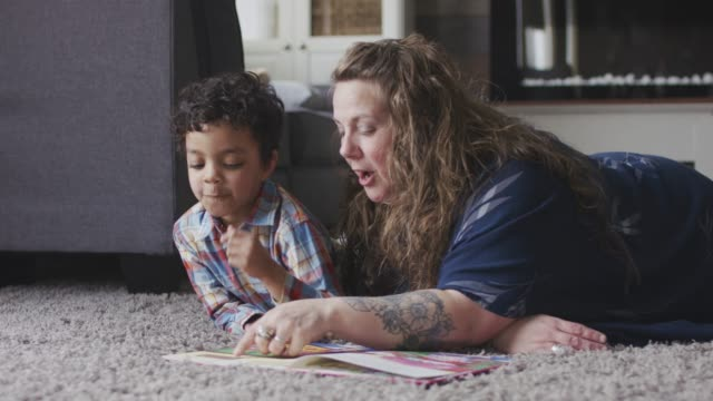 a mother and son read a book together - joy stock videos & royalty-free footage