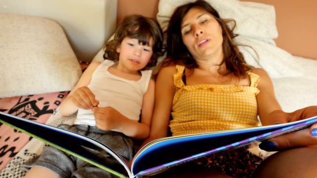 mother and son reading a book - storyteller stock videos & royalty-free footage