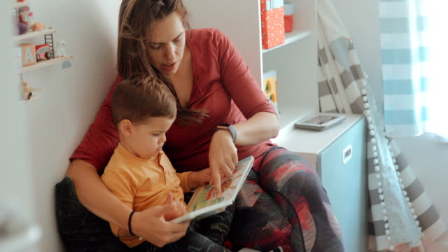 mother and son reading book in kid's bedroom - toddler stock videos & royalty-free footage