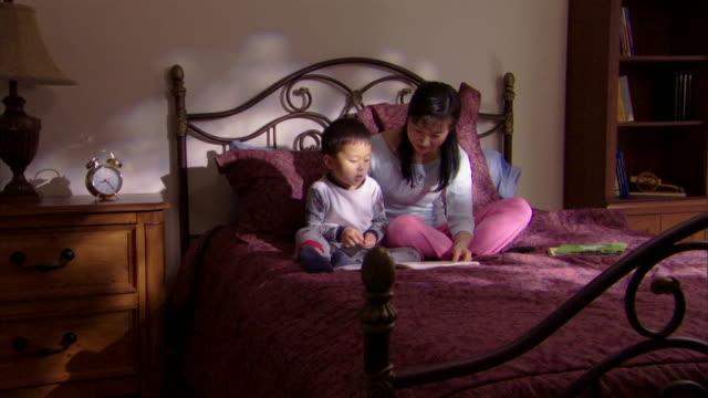 mother and son reading book - andere clips dieser aufnahmen anzeigen 1282 stock-videos und b-roll-filmmaterial