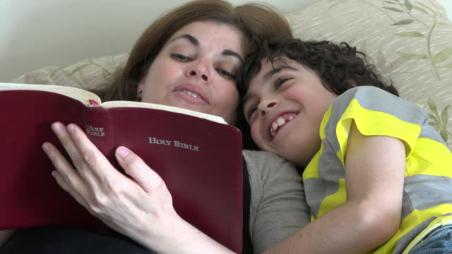 vídeos y material grabado en eventos de stock de mother and son reading the bible on the bed - bible