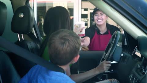 vídeos y material grabado en eventos de stock de mother and son receiving food order from employee of a fast food drive-through - restaurante de comida rápida