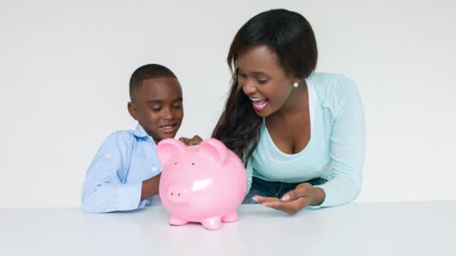 vidéos et rushes de mère et fils, économiser de l'argent pour ses études - tirelire