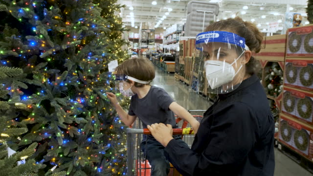 mother and son shopping for christmas trees in a store wearing protective face masks - public celebratory event stock videos & royalty-free footage