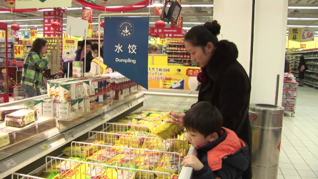 ms mother and son shopping for frozen dumplings in supermarket/ shanghai, china - chinese culture stock videos & royalty-free footage