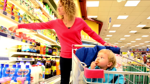 mother and son shopping in a supermarket - supermarket stock videos and b-roll footage