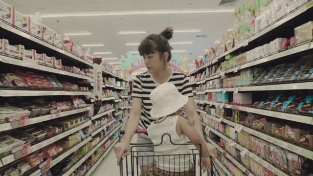 mother and son shopping in a supermarket - shelf stock videos and b-roll footage