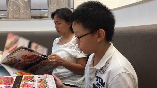 Mutter und Sohn sitzen im Restaurant