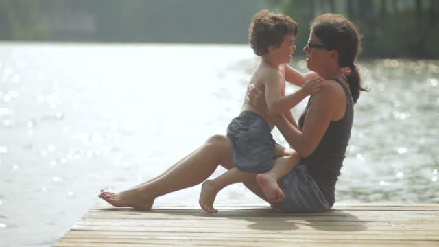 MS Mother and son sitting on dock with hugging and kissing / WOLFEBRO, NH, USA