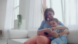 Mother and son sitting on sofa using digital tablet. Happy mom and little boy using tablet with touchscreen together watching a video. Smiling mother and cute boy playing on digital tablet