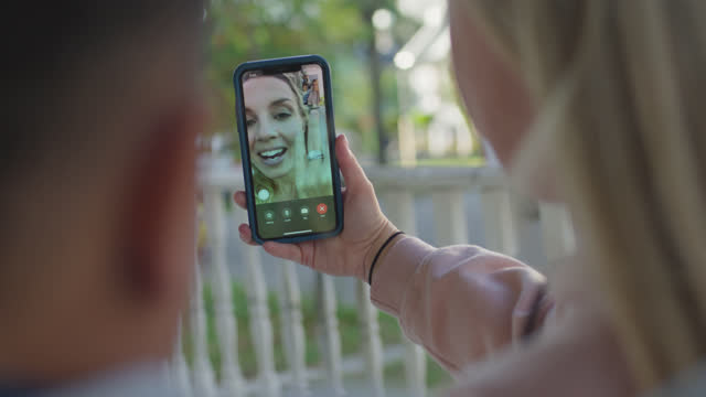 cu mother and son sitting outdoors together use smartphone to talk to young woman via video call - new normal concept stock videos & royalty-free footage