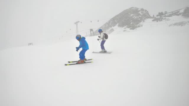 mother and son skiing at glacier in the alps - sci e snowboard video stock e b–roll
