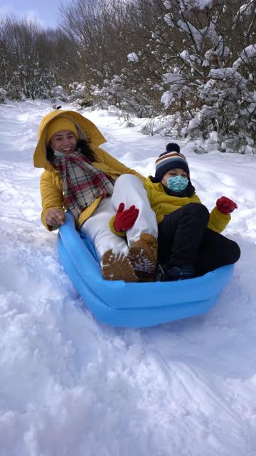 インフレータブルプールで雪の上に母と息子のスライド - 4k垂直ビデオ - ウィンターコート点の映像素材/bロール