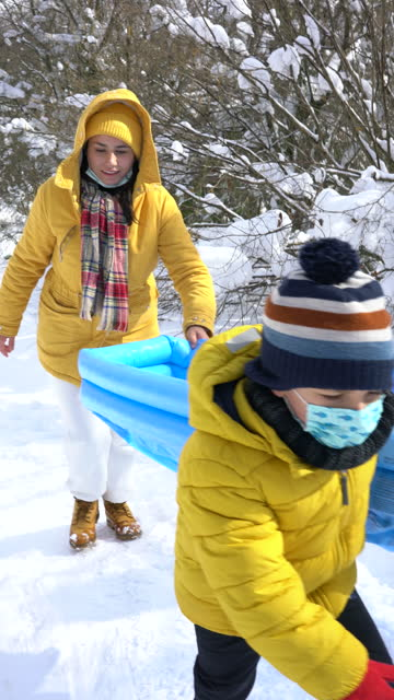 vídeos de stock e filmes b-roll de mother and son slide on snow with inflatable pool - 4k vertical video - 6 7 years