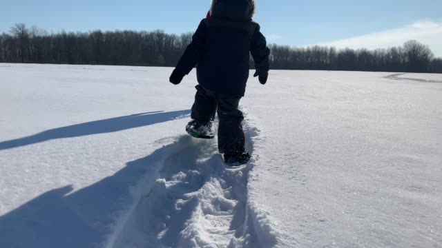 mother and son snowshoeing outdoor in winter after snowstorm - footprint stock videos & royalty-free footage