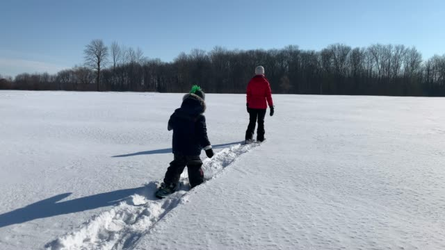 mother and son snowshoeing outdoor in winter after snowstorm - family with one child stock videos & royalty-free footage