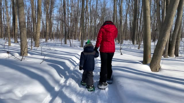 Mother and Son Snowshoeing Outdoor in Winter After Snowstorm