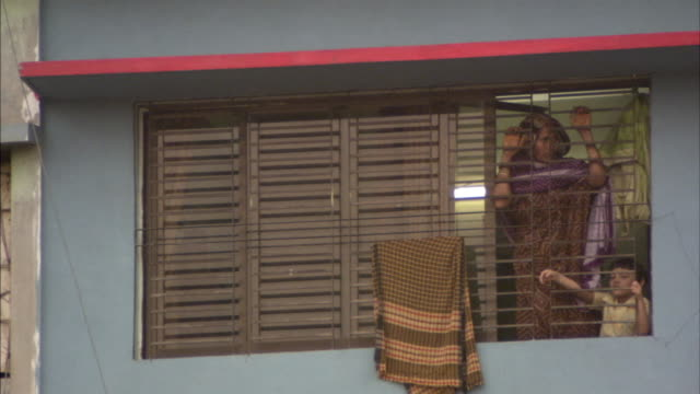 ms, mother and son (4-5) standing against bars in window, dhaka, bangladesh - dhaka stock videos and b-roll footage