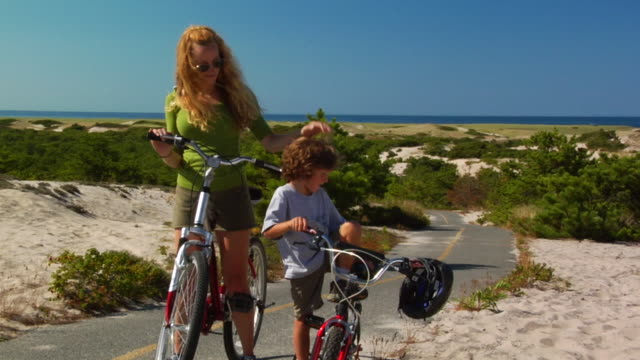 MS, Mother and son (4-5) standing at bikes on coastal road, Provincetown, Massachusetts, USA