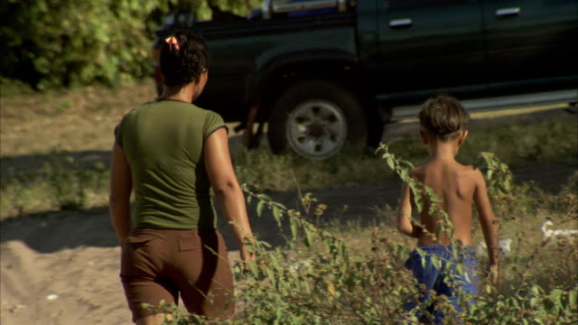 a mother and son stroll on a dirt road in a chilean village. available in hd. - two generation family stock videos & royalty-free footage