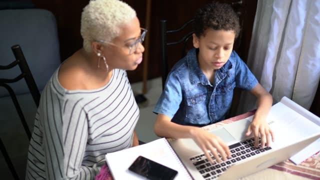 vídeos y material grabado en eventos de stock de madre e hijo estudiando con portátil en una clase en línea en casa - evento virtual