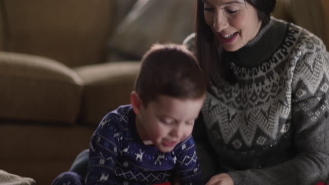 mother and son unwrapping christmas gifts - pyjamas stock videos & royalty-free footage